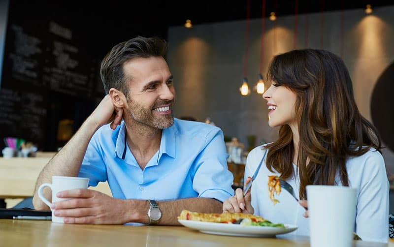 couple having lunch in a cafe with mans hand supporting his head while listening