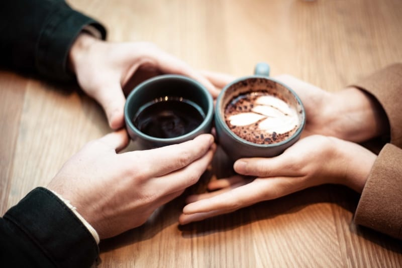 man and woman holding ceramic mugs with coffee