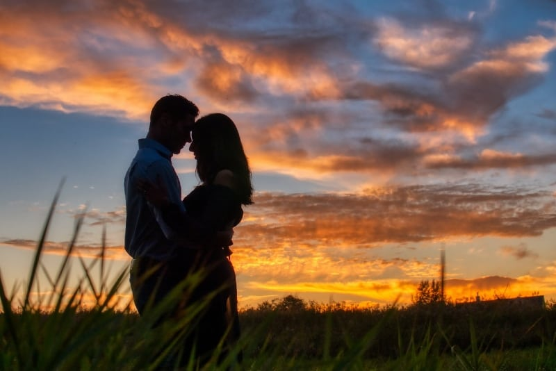 man and woman hugging outdoor during sunset
