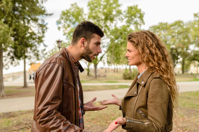 couple in brown jackets arguing in the middle of the park