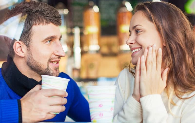 couple inside a cafe talking with the man holding a cup and woman giggles