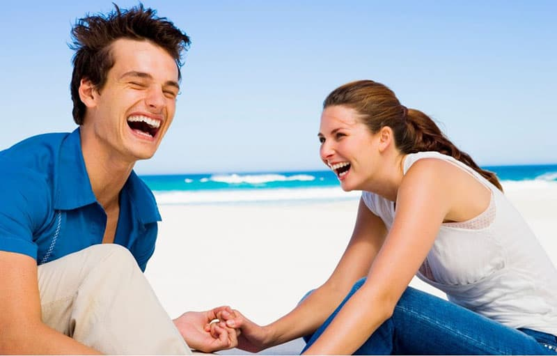 couple laughing in the beach both wearing blue and white tops and pants