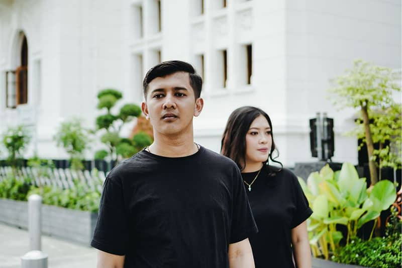 couple looking at different direction standing outdoors wearing black shirts