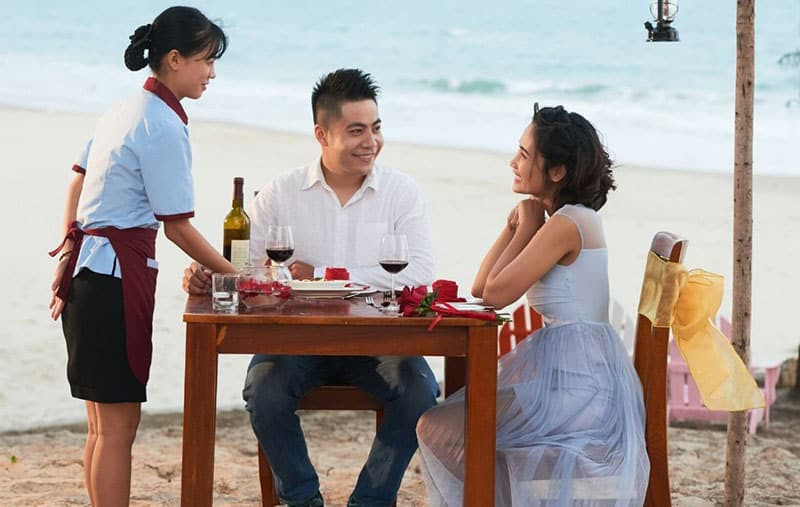 couple lunchdate by the beach with a waitress serving them