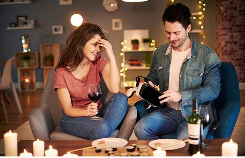 couple on date with sushi and wine glass and virtual reality game
