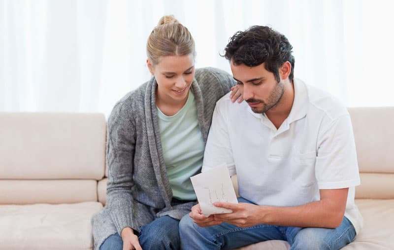 couple opening an envelope with woman holding man's shoulder