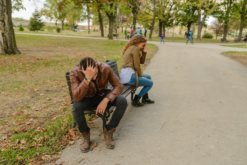couple sitting apart in the bench after a fight
