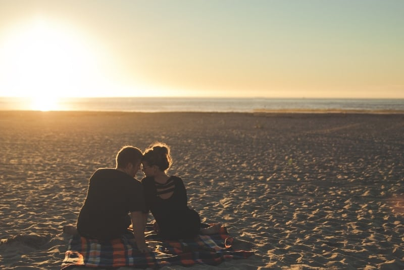 man and woman sitting on blanket on beach during sunset