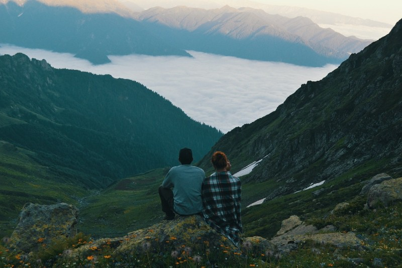 man and woman sitting on rock looking at mountain