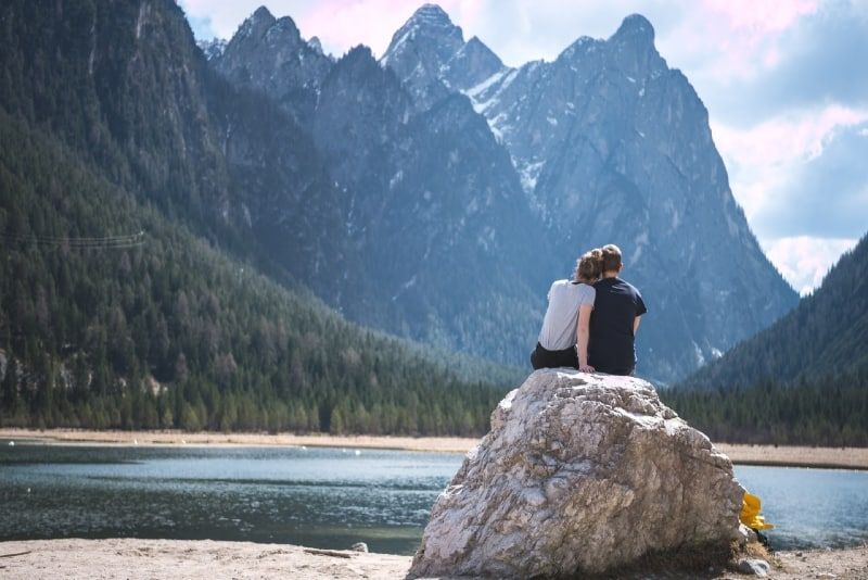 woman and man sitting on rock and looking at lake