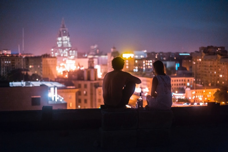 man and woman sitting in front of high-rise buildings