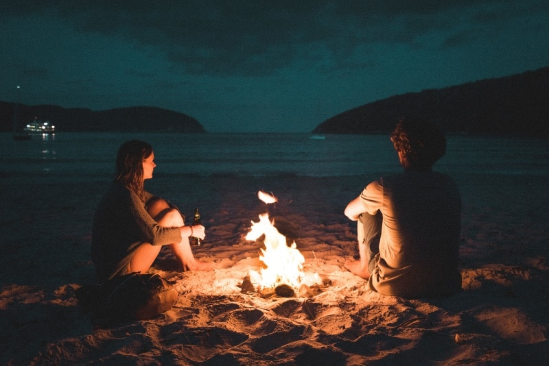 man and woman with bonfire sitting on seashore
