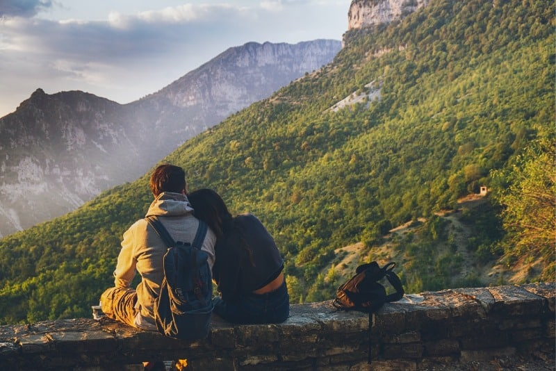 man with backpack and woman sitting outdoor looking at mountain