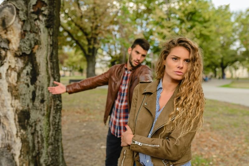 man and woman in brown jackets standing near tree