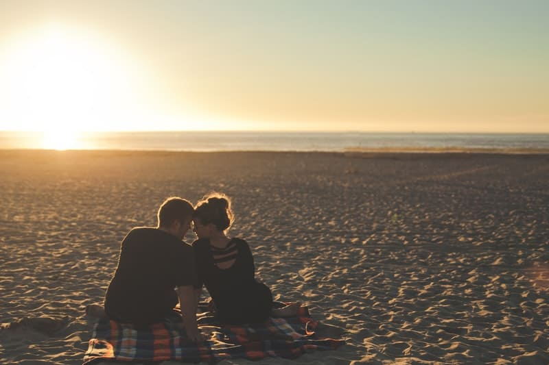 couple watching the sun while sitting on a picnic mat placed on seashore