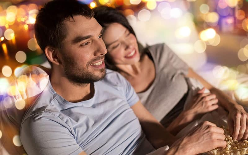 couple watching tv with popcorn and dim lights