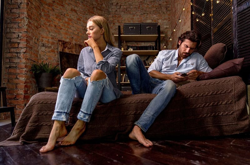 couple with relationship problem sitting on sofa with man texting on phone with woman beside him