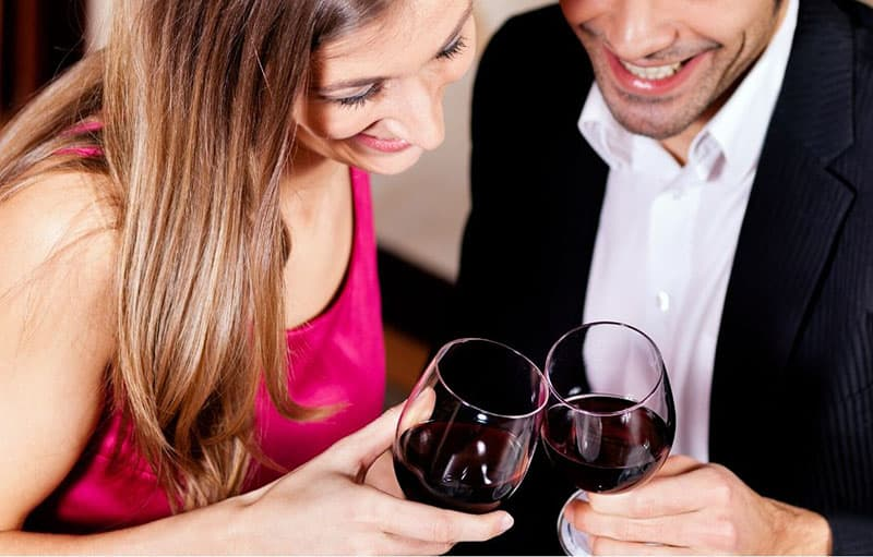 couple's wine glass bumped with couple close to each other in downward angle