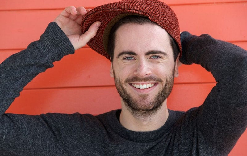 cute handsome guy with beard holding his hat