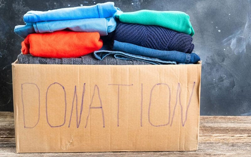 donation box filled with old clothes of different colors