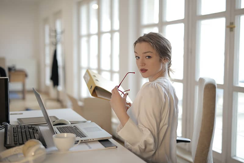 elegant businesswoman holding folder in office