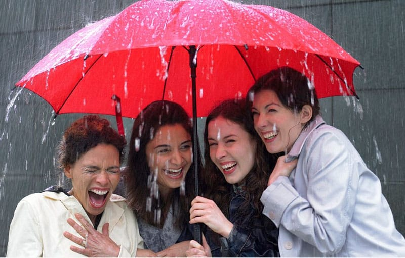four women sharing under a red umbrella on a rainy day