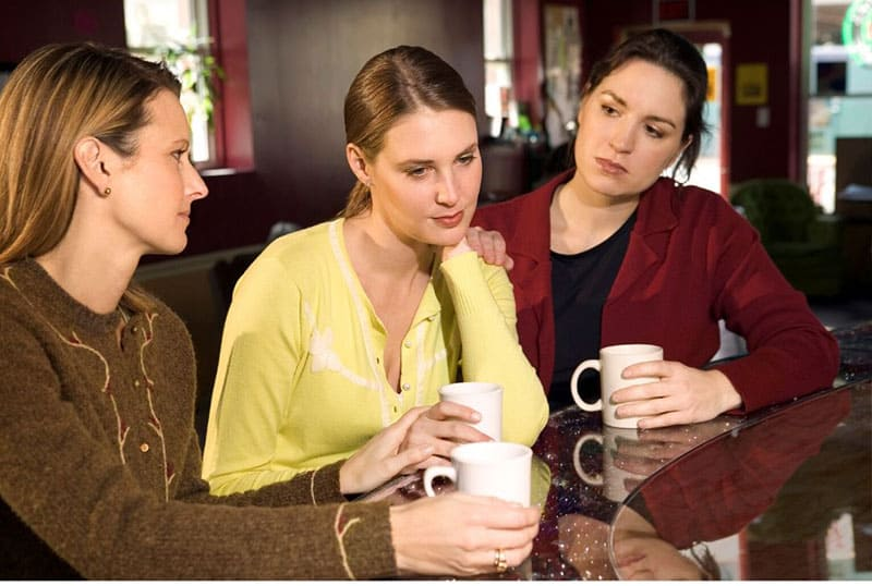 friends consoling a woman in pain while having a hot beverage in the dining table