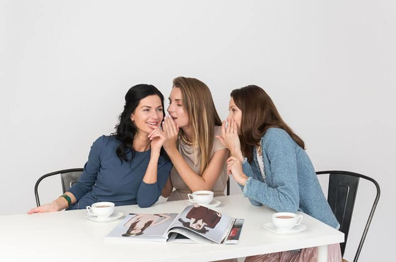 girls sharing exciting news over coffee with magazines on the table where they seated