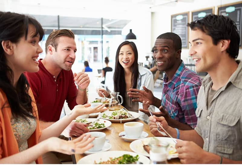 group of friends eating while chatting inside a cafe