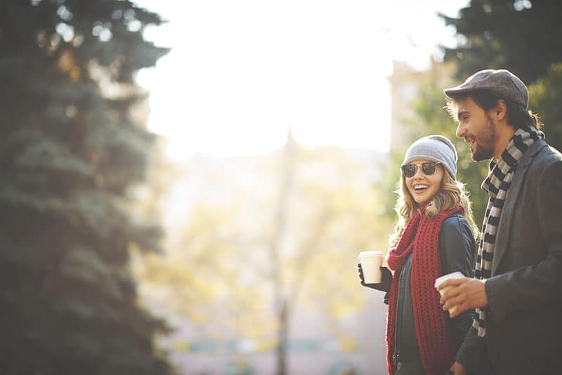 happy couple walking and holding coffee cups