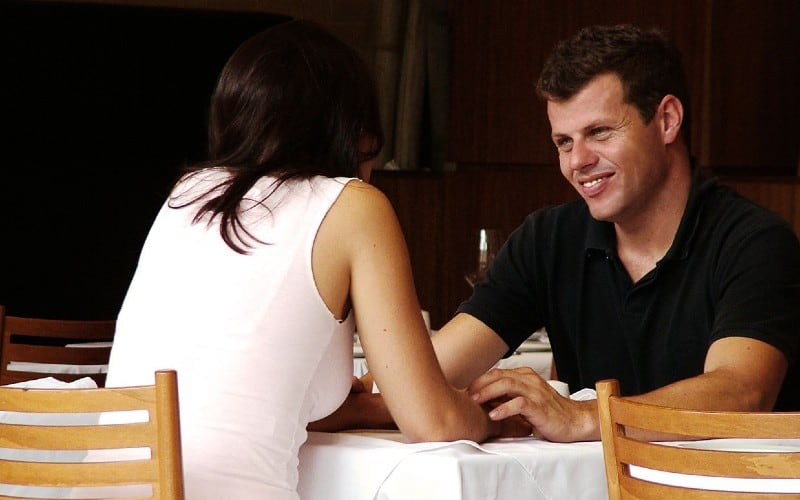 Happy man in front of woman at a table