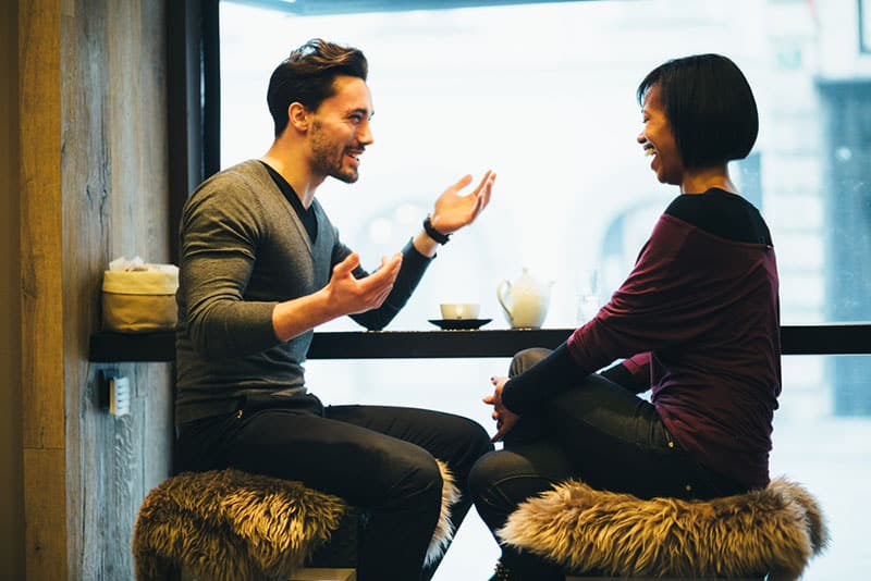 happy man talking to smiling woman at cafe