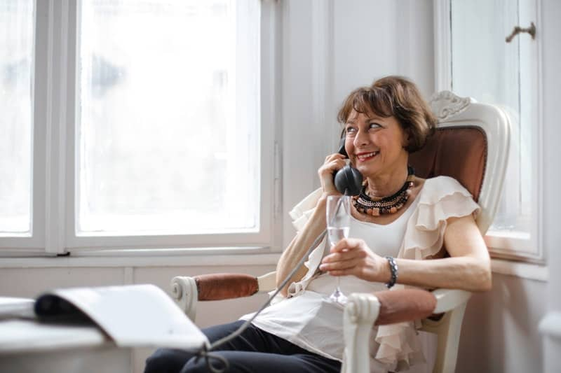 happy middle aged woman making phone call while holding a glass and sitting near the window