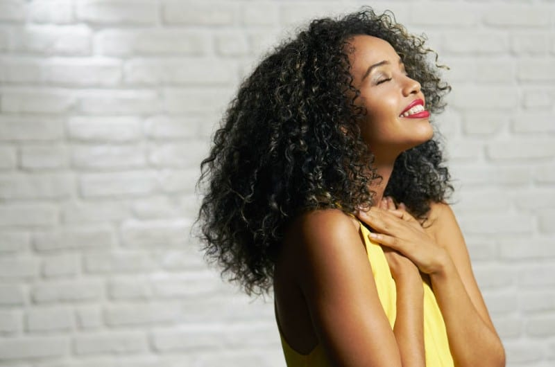 Happy gratefull african american woman wearing yellow top
