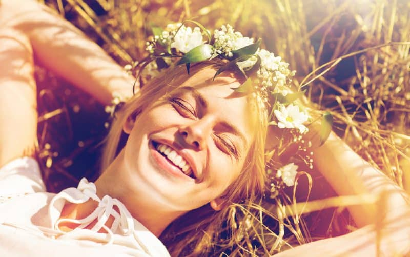 Happy woman lying on straw weating flower wreath