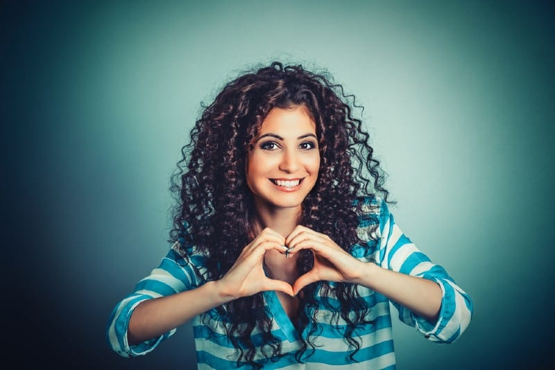 Happy brunette woman making heart shape with hands