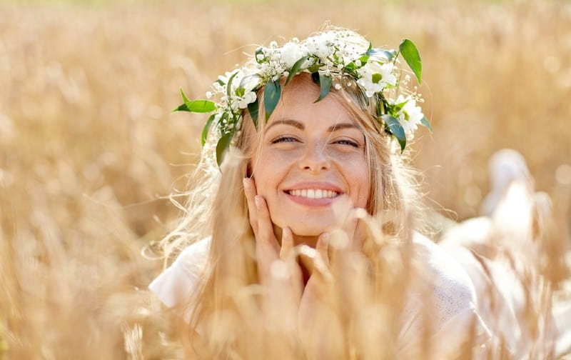 Happy beautiful blonde woman wearing wreath of flowers lying on the ground in a cereal field