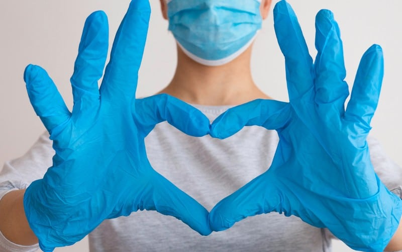 Heart shape with nurse hands covered in blue surgical gloves