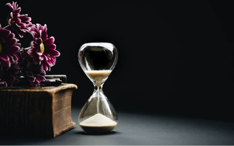 Hourglass and flowers in dark background