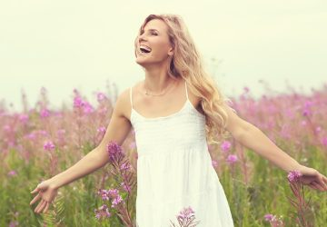 Happy woman in white dress on a field with flowers