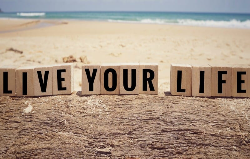 live your life message on wooden cubes on the-beach