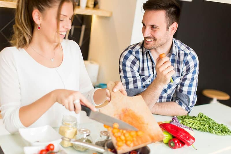 man and woman cooking with woman holding knife pouring vegetables