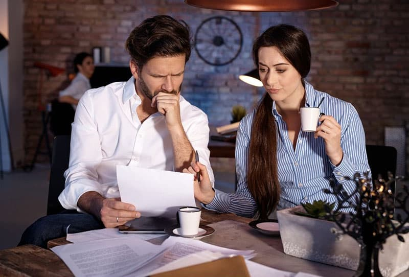 man and woman discussing over on papers while drinking coffee