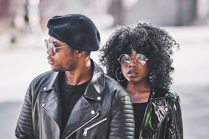 man and woman in black leather jackets standing together