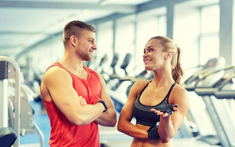 man and woman in the gym talking in gym attire