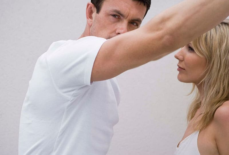 man and woman in white tops with guys hand on the wall where woman leans