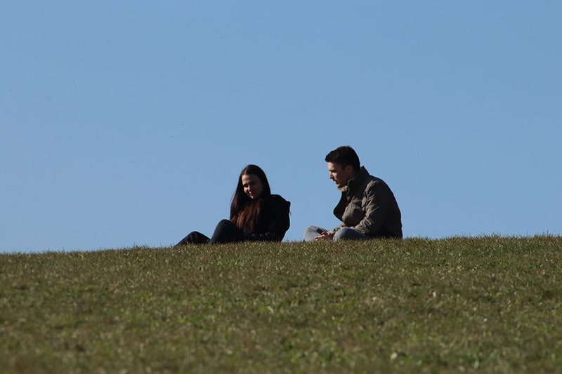man and woman sitting on green grass field during daytime