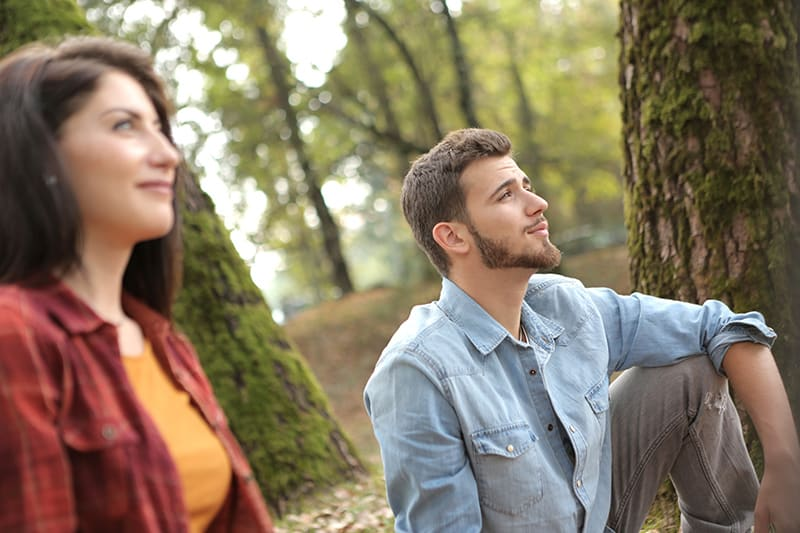 man and woman thoughtfully looking away while sitting on the ground