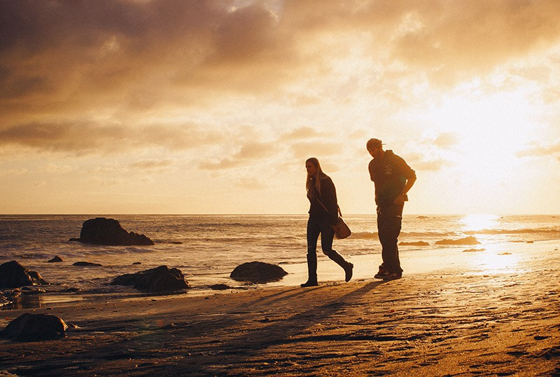 man and woman walking on the seashore during sunset
