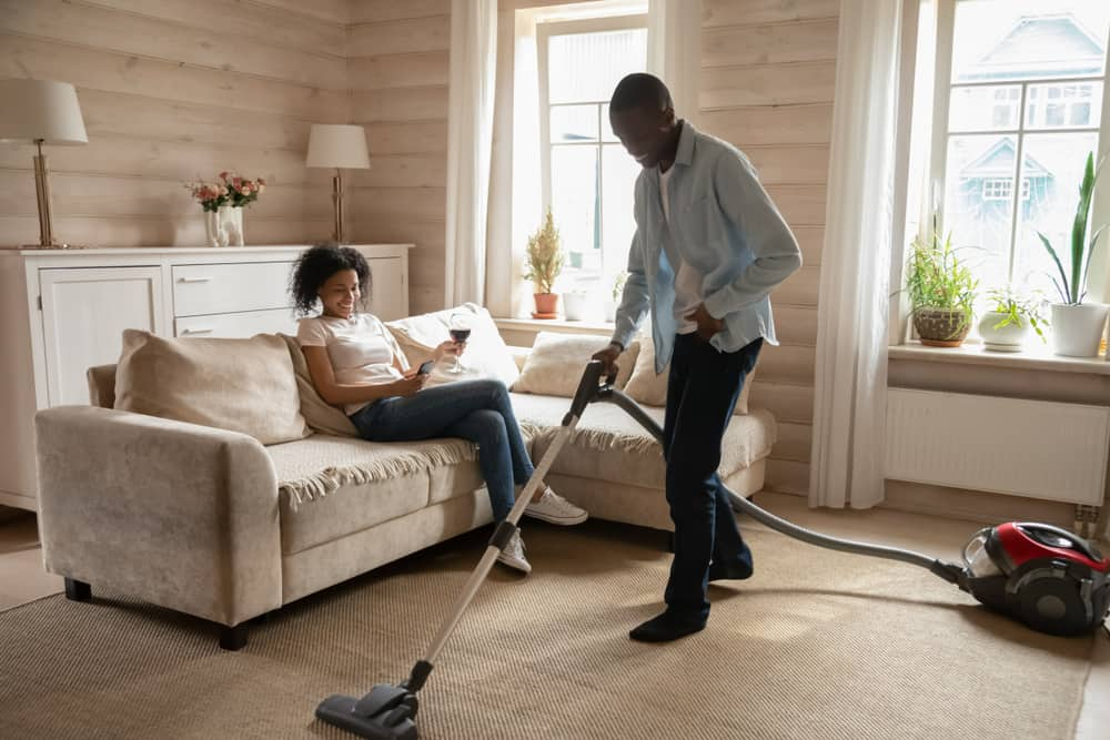 man cleaning house while woman sitting